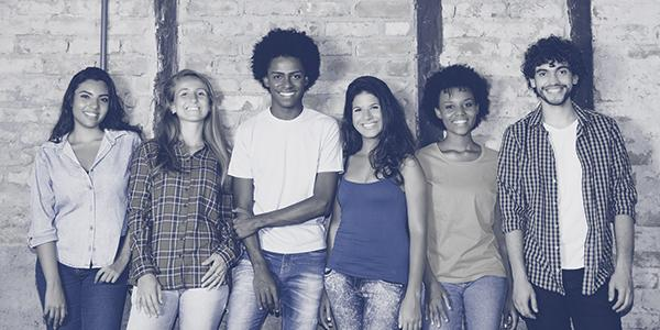Group of teens standing against a wall smiling